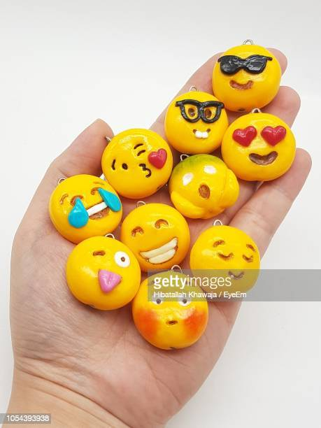 cropped hand holding emojis against white background - emoji stock pictures, royalty-free photos & images