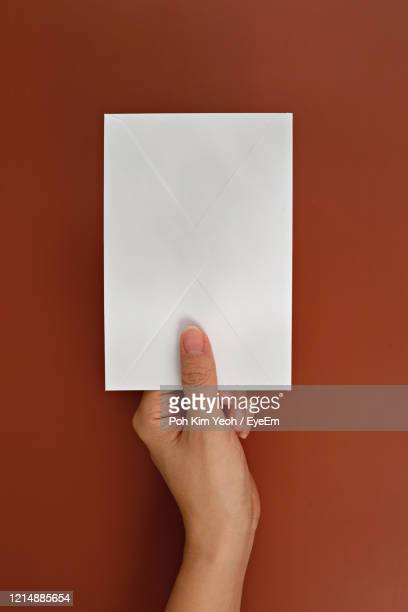 cropped hand holding envelope over brown background - people stock pictures, royalty-free photos & images