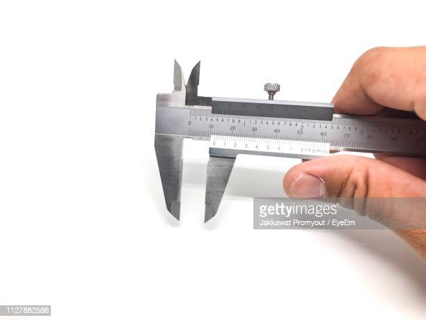 cropped hand holding equipment against white background - measuring stock photos and pictures