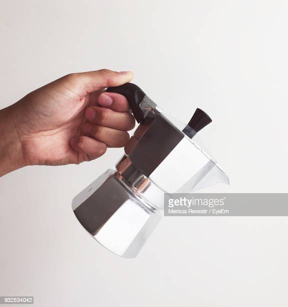 Cropped Hand Holding Espresso Maker Against White Background