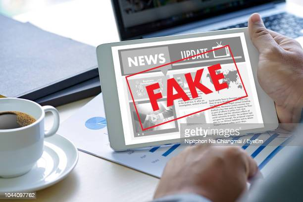 cropped hand holding fake news in digital tablet - fake stock pictures, royalty-free photos & images