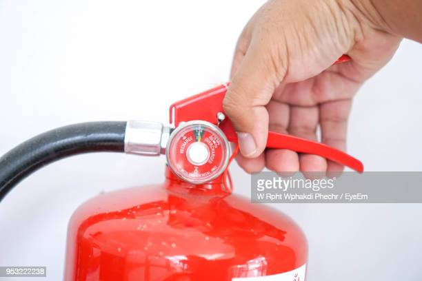 cropped hand holding fire extinguisher against white background - fire extinguisher stock photos and pictures