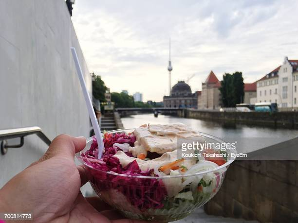 Cropped Hand Holding Food In Container By Spree River In City