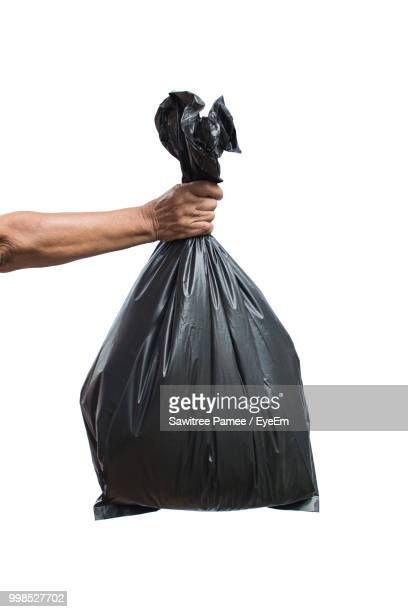cropped hand holding garbage bag against white background - bin bag stock pictures, royalty-free photos & images