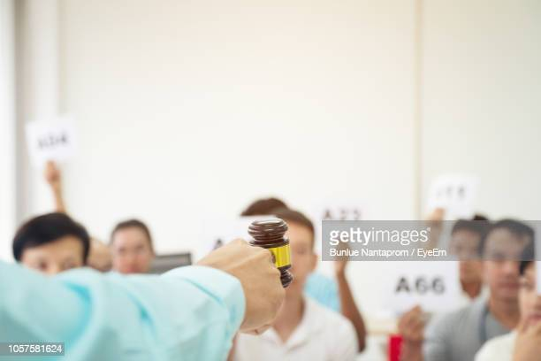 cropped hand holding gavel against people during auction - bid stock pictures, royalty-free photos & images