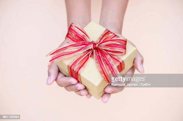 Cropped Hand Holding Gift Box Against Colored Background