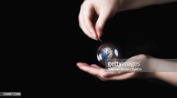 Cropped Hand Holding Globe Against Black Background