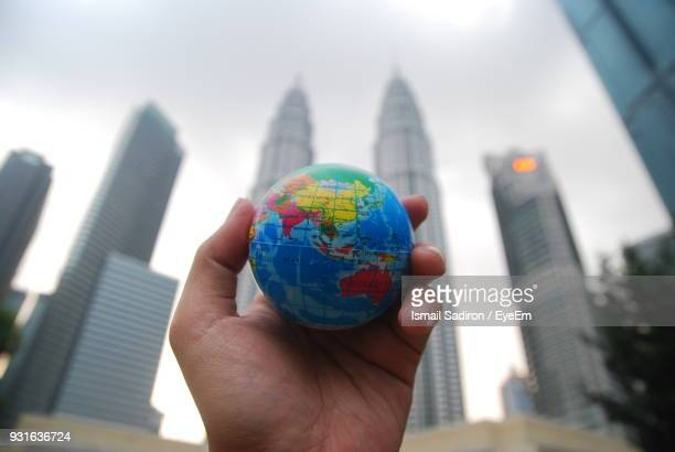 Cropped Hand Holding Globe Against Petronas Towers In City