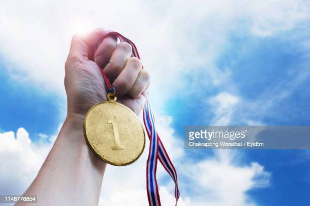 cropped hand holding gold medal against sky - gold medal stock pictures, royalty-free photos & images