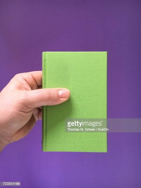 Cropped Hand Holding Green Diary Against Purple Background