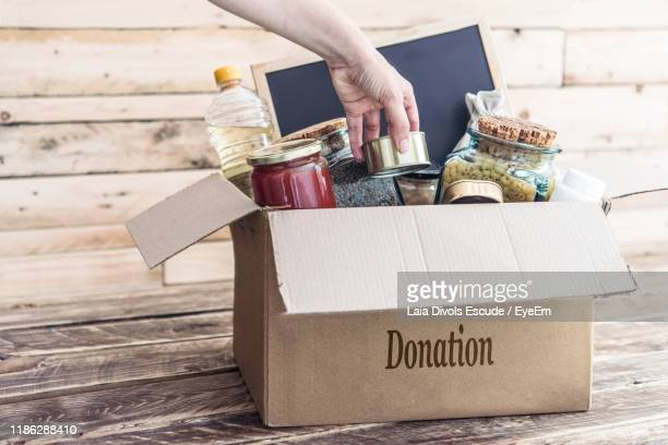 cropped hand holding groceries over cardboard box - charitable donation stock pictures, royalty-free photos & images