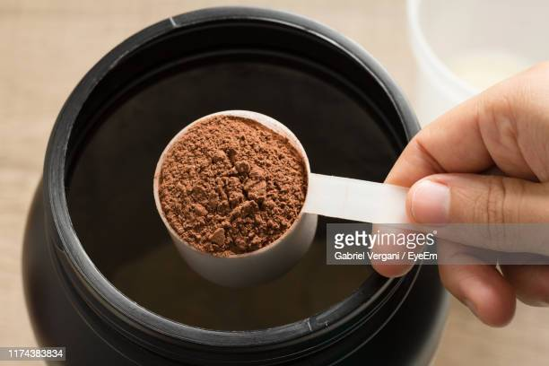 cropped hand holding ground protein in scoop at table - protein stock pictures, royalty-free photos & images