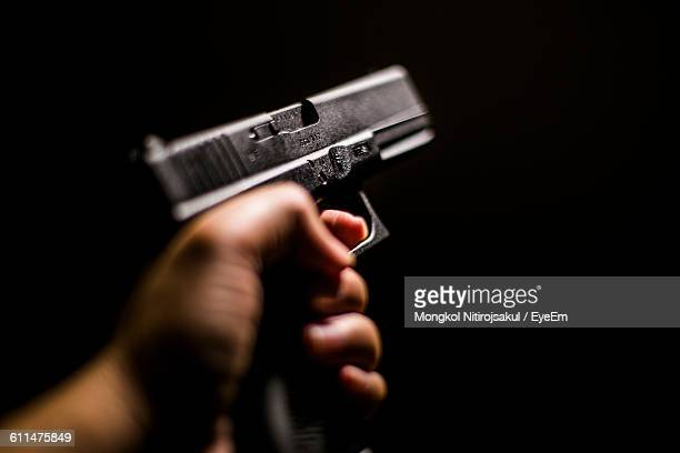cropped hand holding gun against black background - armi foto e immagini stock