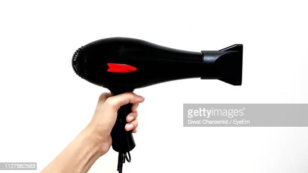 cropped hand holding hair dryer against white background - secador de cabelo - fotografias e filmes do acervo