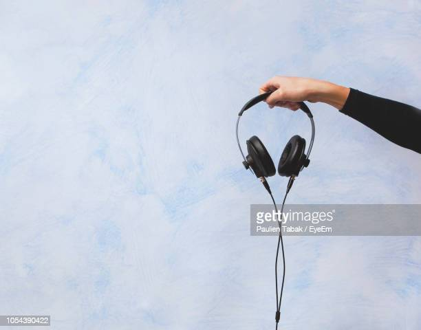 Cropped Hand Holding Headphones Against Wall