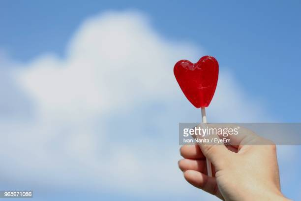 Cropped Hand Holding Heart Shape Candy Against Sky