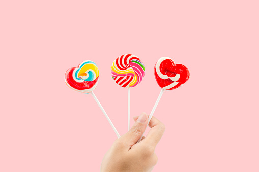 Cropped Hand Holding Heart Shape Lollipop Against Pink Background - gettyimageskorea