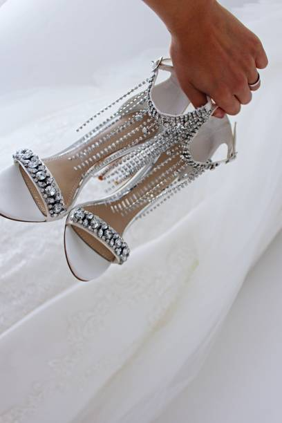 Cropped Hand Holding High Heels By Wedding Dress