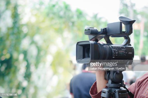 cropped hand holding home video camera outdoors - television camera stock pictures, royalty-free photos & images