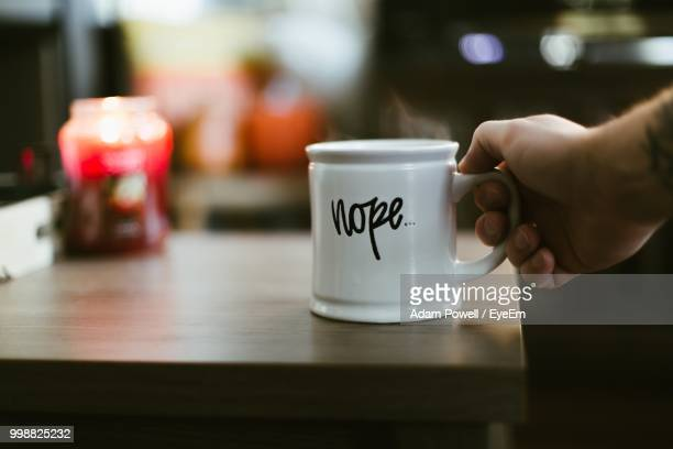 cropped hand holding hot coffee cup on table - mug stock pictures, royalty-free photos & images