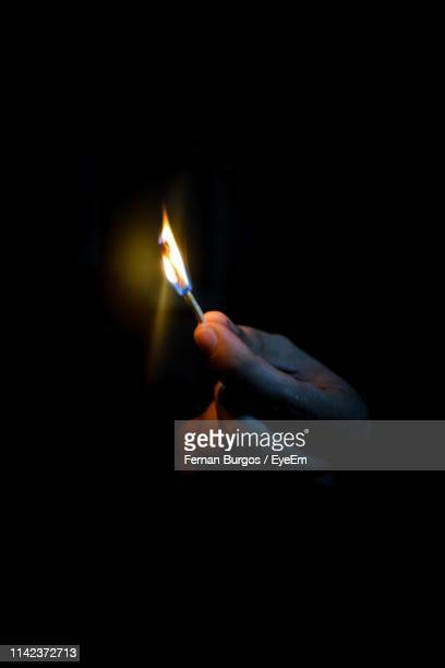 cropped hand holding illuminated matchstick in darkroom - match lighting equipment stock photos and pictures