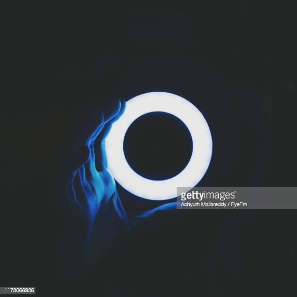 cropped hand holding illuminated ring in darkroom - people stock pictures, royalty-free photos & images