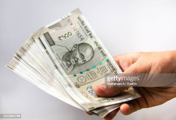 cropped hand holding indian currency against white background - indian currency stock photos and pictures