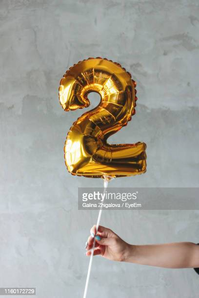 cropped hand holding inflatable number 2 shaped balloon against wall - number 2 stock pictures, royalty-free photos & images