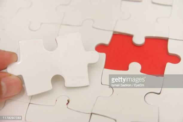 cropped hand holding jigsaw piece on red background - joining the dots - fotografias e filmes do acervo