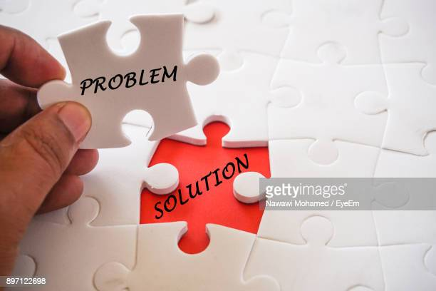 cropped hand holding jigsaw piece - solutions stock pictures, royalty-free photos & images