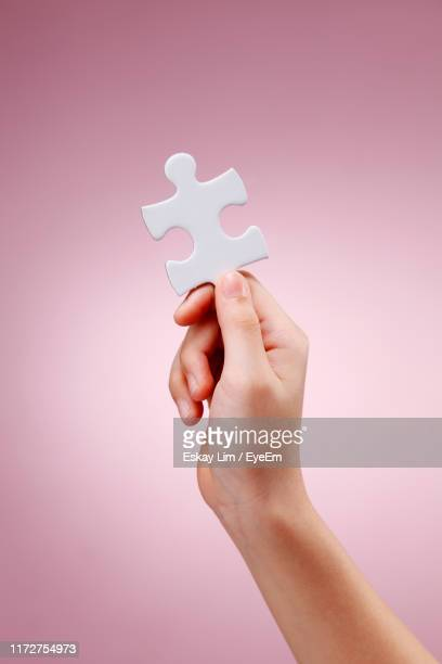 cropped hand holding jigsaw pieces against pink background - 電動糸のこ ストックフォトと画像