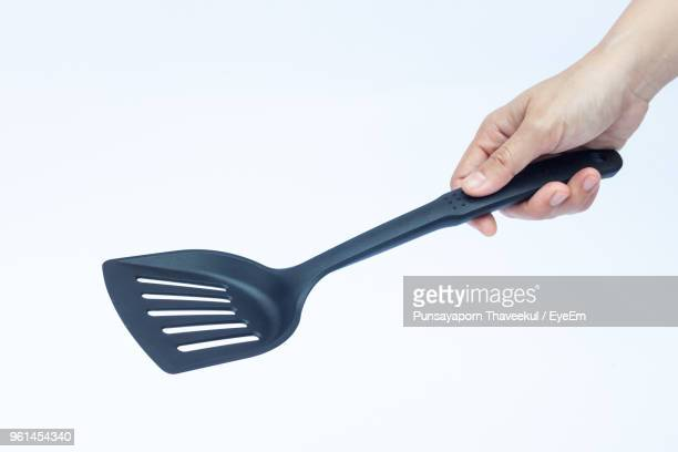 Cropped Hand Holding Kitchen Utensils Over White Background