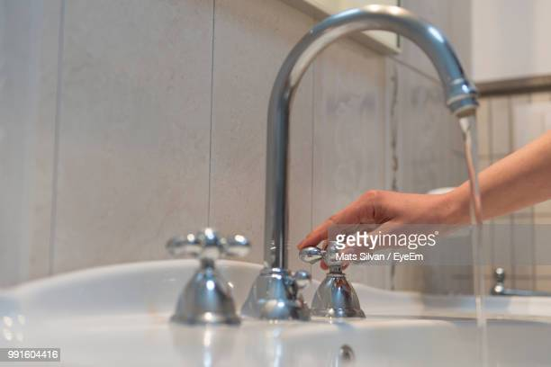 Cropped Hand Holding Knob On Sink