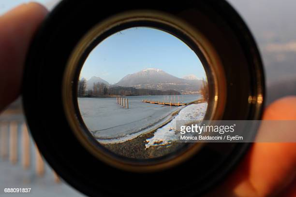 Cropped Hand Holding Lens Against Frozen Lake By Mountains