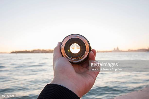 cropped hand holding lens against sea during sunset - lens optical instrument stock photos and pictures