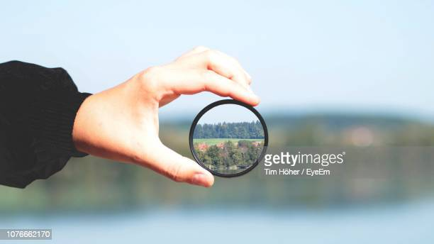 cropped hand holding lens with reflection - image focus technique stock pictures, royalty-free photos & images