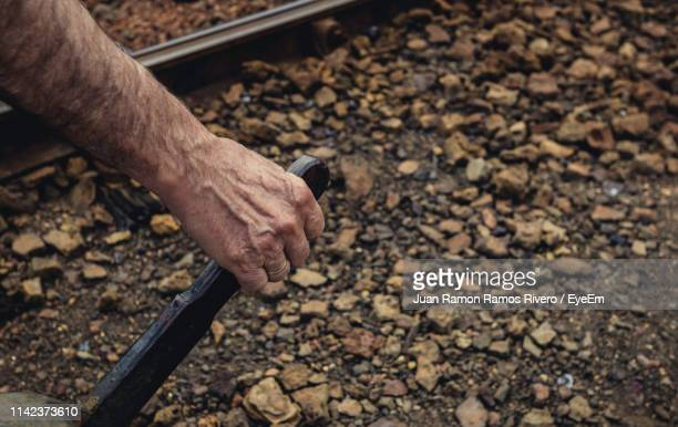 Cropped Hand Holding Lever By Railroad Track