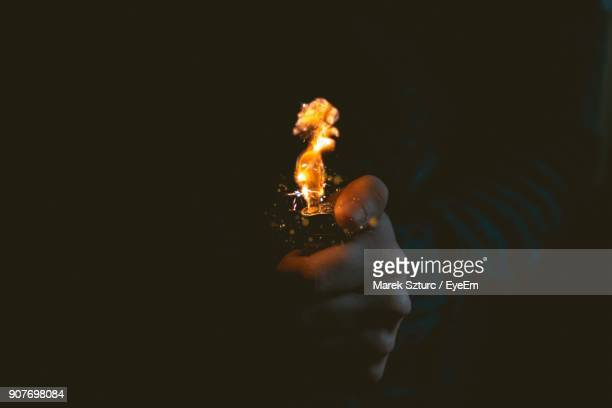 cropped hand holding lighter against black background - cigarette lighter stock pictures, royalty-free photos & images