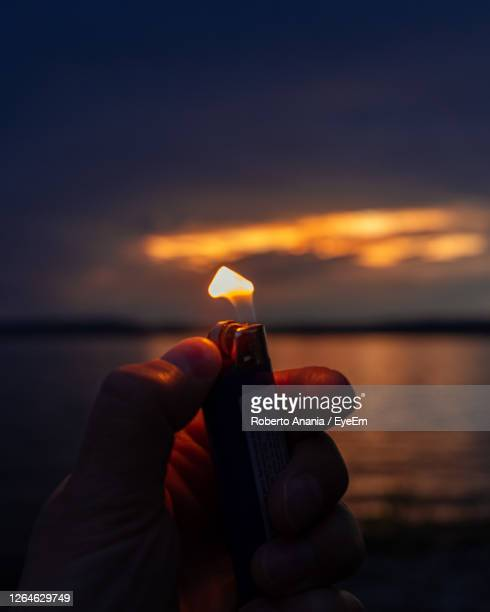 cropped hand holding lit cigarette lighter at beach during sunset - unusual angle stock pictures, royalty-free photos & images