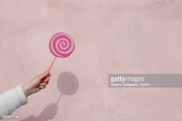 Cropped Hand Holding Lollipop Against Wall During Day