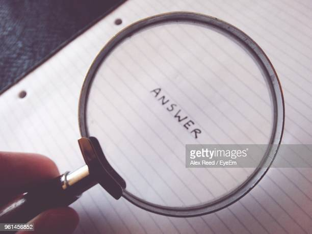 Cropped Hand Holding Magnifying Glass On Text