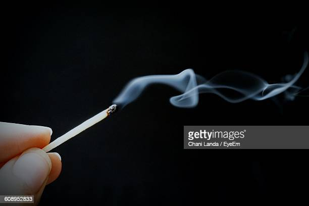 Cropped Hand Holding Matchstick With Smoke Against Black Background