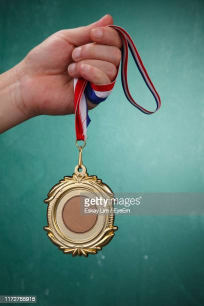 cropped hand holding medal against green background - gold medalist stock pictures, royalty-free photos & images