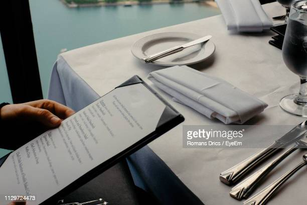 cropped hand holding menu at table in restaurant - menu stock pictures, royalty-free photos & images