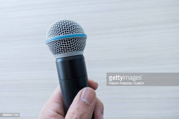 Cropped Hand Holding Microphone Against Wall