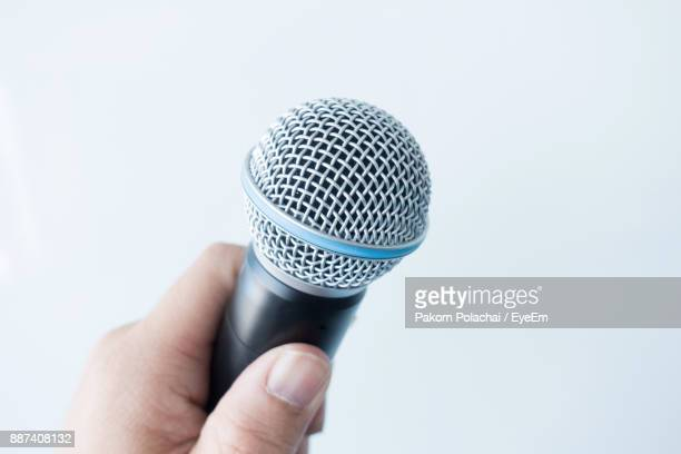 Cropped Hand Holding Microphone Against White Background