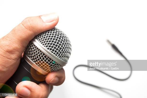 Cropped Hand Holding Microphone Over White Background