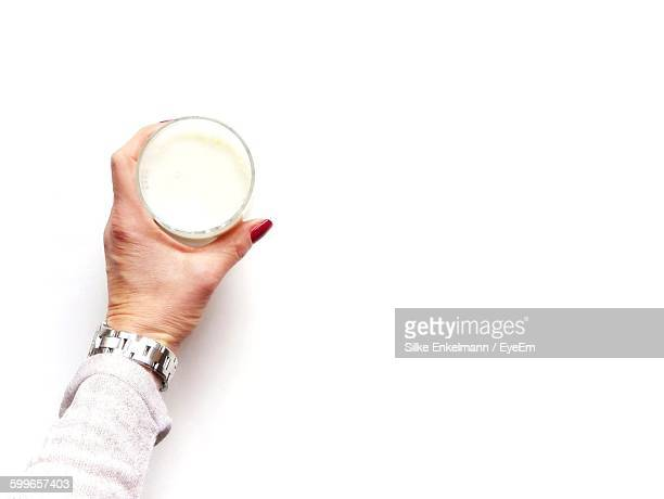 Cropped Hand Holding Milk Glass Against White Background