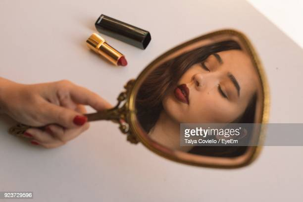 cropped hand holding mirror with reflection - hand mirror stock photos and pictures