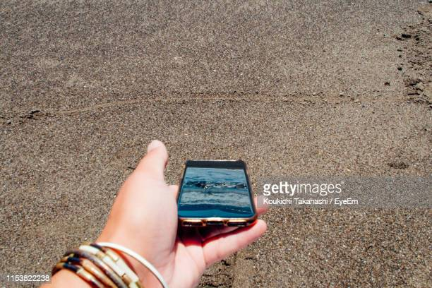 Cropped Hand Holding Mobile Phone At Beach